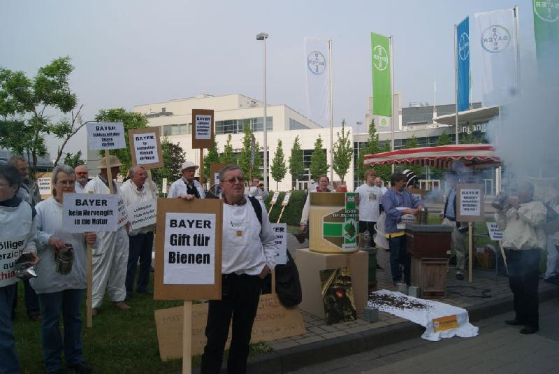 Demonstranten vor der Bayer-Hauptversammlung mit Schildern z.B.: «Bayer. Gift für Bienen.».